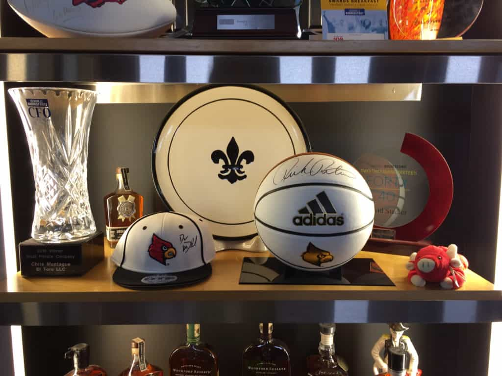 Signed University of Louisville basketball by rick pitino and baseball cap by dan mcdonnell at the El toro office in louisville ky